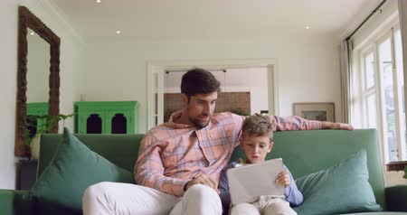 fele olyan hosszú : Front view of Caucasian father and son using digital tablet on sofa at home. They are sitting together on sofa 4k