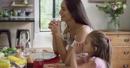 clasped : Side view of Caucasian mother and daughter praying before having meal at dining table. They are sitting together 4k