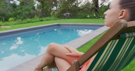 bord de piscine : Close-up of thoughtful Caucasian woman in swimwear relaxing on chair near swimming pool in the backyard. She is looking away 4k