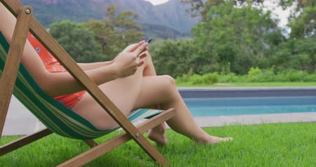 tárcsázás : Close-up of Caucasian woman relaxing on beach chair in the backyard. She is using mobile phone 4k