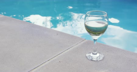 хрупкость : Close-up of drink in glass near swimming pool in the backyard. Turquoise water in the backyard 4k
