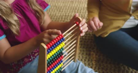 sitting floor : Close-up of Caucasian mother teaching her daughter mathematics on abacus at home. She is playing with abacus 4k