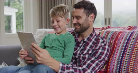 ailelerin : Front view of Caucasian father and son using digital tablet on sofa at home. They are sitting together on sofa 4k