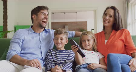 changing channel : Front view of Caucasian family watching television together in living room at home. They are smiling and having fun 4k Stock Footage