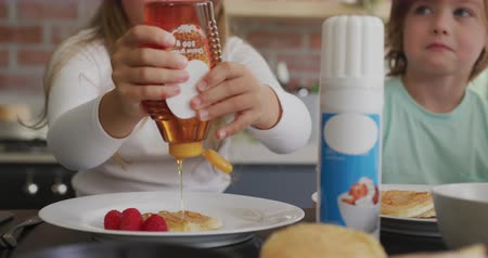 garnishing : Close-up of Caucasian girl putting honey on pancake at dining table in a comfortable home. She is garnishing food 4k Stock Footage