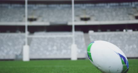absence : Close-up of rugby ball on a grass in the stadium. Empty stadium in background 4k