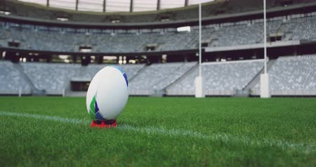 pavilion : Close-up of rugby ball on a grass in the stadium. Empty stadium in background 4k
