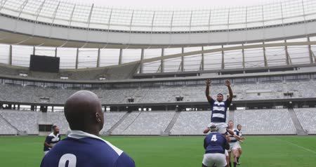jarse : Front view of diverse male rugby players playing rugby match in stadium. They are passing rugby ball 4k Stok Video