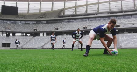 konkurenti : Front view of diverse male rugby players playing rugby match in stadium. Caucasian male player passing rugby ball 4k