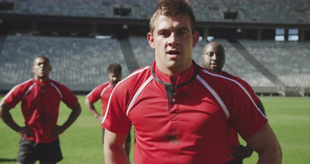 jarse : Close-up of Caucasian male rugby player standing with hands on hip in stadium. He is tired and looking at camera 4k