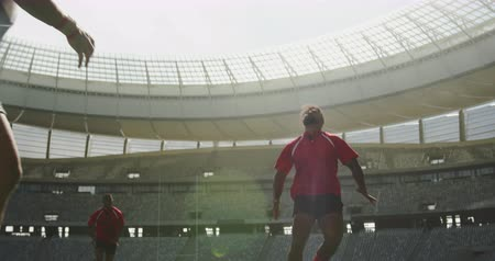 снасти : Low angle view of diverse rugby players playing rugby match in stadium. They are tackling each other 4k