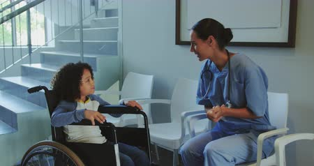 lobby : Front view of Caucasian female doctor interacting with disabled boy in the corridor at hospital. They are smiling 4k