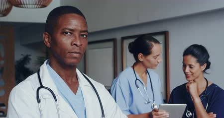 etnia africano : Front view of African american doctor with arm crossed looking at camera at lobby in hospital. Female doctors discussing over digital tablet 4k Stock Footage