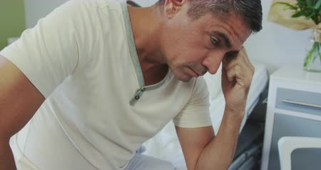 çene : Front view of thoughtful Caucasian male patient looking away in the hospital ward, He is tensed and worried 4k