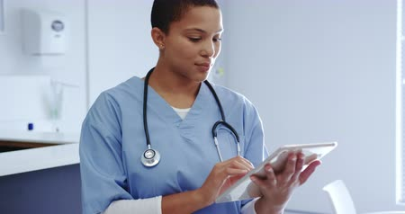 病院 : Front view of African American female doctor using digital tablet in hospital. She is smiling and looking at camera 4k