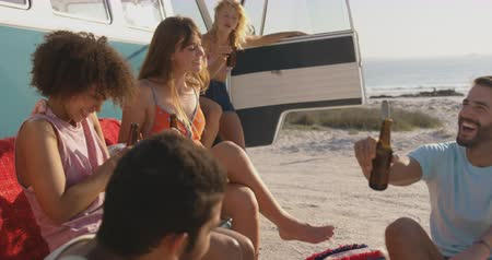 пляжная одежда : Handheld side view of a multi-ethnic group of young adult friends drinking bottles of beer, having fun and talking by a camper van on a beach. Summer fun with friends, they are on a road trip to the beach 4k
