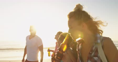 roupa de praia : Close up side view of a multi-ethnic group of happy young adult friends walking on a beach at sunset, drinking bottles of beer and carrying a cool box and beach bags. Backlit. Summer fun with friends, they are on a road trip to the beach 4k