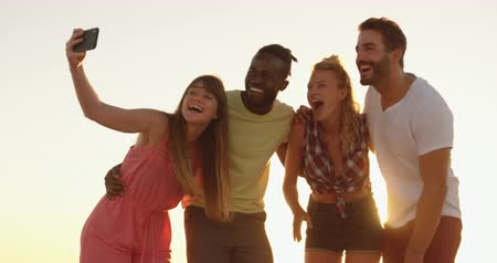 bronzeada : Close up portrait of a multi-ethnic group of happy young adult friends standing on a beach at sunset, embracing and taking selfies. Backlit. Summer fun with friends, they are on a road trip to the beach 4k