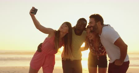 использование : Front view of a multi-ethnic group of young adult friends standing on a beach at sunset, embracing and taking selfies. Backlit. Summer fun with friends, they are on a road trip to the beach 4k Стоковые видеозаписи