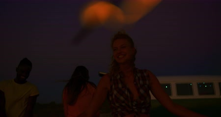 csillagszóró : Close up of a young Caucasian woman on a beach at night with her friends, jumping around and having fun, waving glowing sparklers. Summer Sunset Party on the beach with friends having fun 4k Stock mozgókép