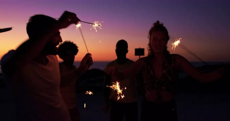 tendo : Close up of a multi-ethnic group of young adult friends in silhouette on a beach at sunset, dancing around and having fun waving glowing sparklers by their camper van. Summer Sunset Party on the beach with friends having fun 4k