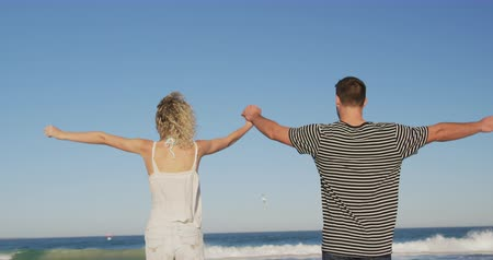 пляжная одежда : Back view close up of a young Caucasian couple standing on a beach holding hands and raising their arms in the air. Young friends having summer fun on the beach together 4k