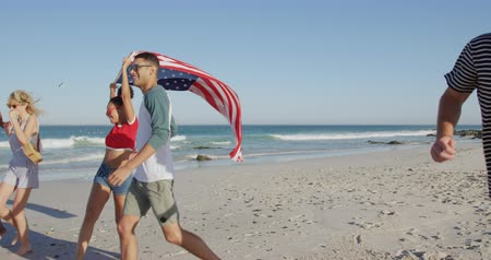 bronzeada : Close up side view of a multi-ethnic group of happy young adult friends having fun running, carrying a US flag and playing around as they walk along a beach. Young friends having summer fun on the beach together 4k Vídeos