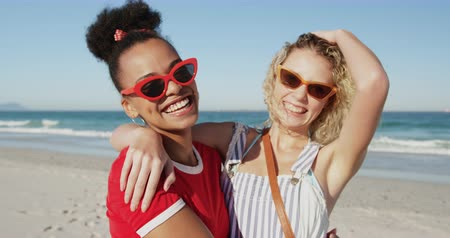 пляжная одежда : Close up front view of two female friends, a young African American and a young Caucasian woman, standing on a beach wearing sunglasses, laughing and embracing. Young friends having summer fun on the beach together 4k Стоковые видеозаписи