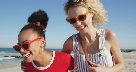 bronzeada : Close up view of two female friends, a young African American and a young Caucasian woman, walking on a beach wearing sunglasses, laughing and embracing. Young friends having summer fun on the beach together 4k Vídeos