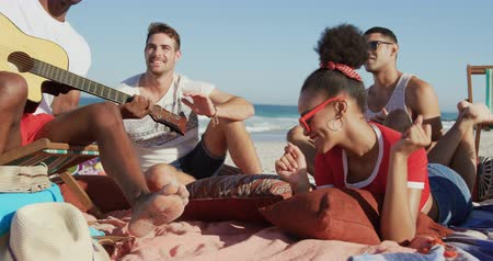 roupa de praia : Close up of a multi-ethnic group of happy young adult male and female friends, sitting on a beach together listening to a young African AMerican man singing and playing playing a guitar. Young friends having summer fun on the beach together 4k