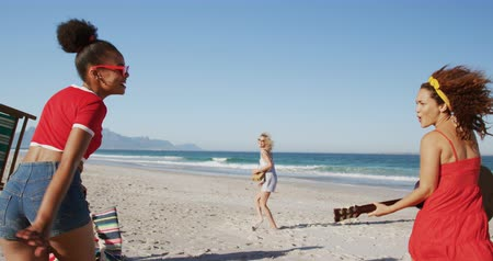 bronzeada : Close up back view of a multi-ethnic group of female friends, walking along a beach together playing a guitar and carrying a deck chair. Young friends having summer fun on the beach together 4k
