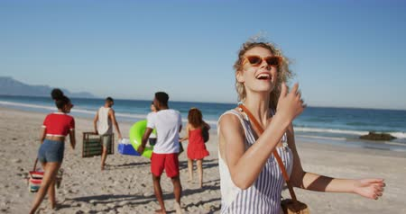 turning off : Close up of a young Caucasian woman walking along a beach behind her friends, turning round and beckoning to someone. Young friends having summer fun on the beach together 4k Stock Footage