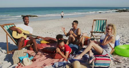 на камеру : A multi-ethnic group of happy young adult male and female friends, sitting on a beach together listening to a young African American man singing and playing a guitar. Young friends having summer fun on the beach together 4k
