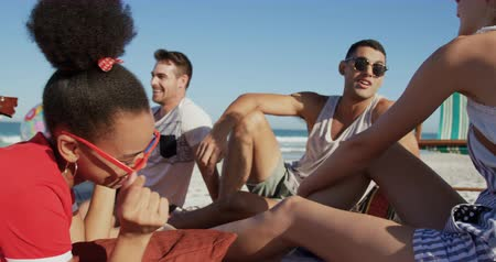 пляжная одежда : Close up of a multi-ethnic group of happy young adult male and female friends, sitting on a beach together talking. Young friends having summer fun on the beach together 4k