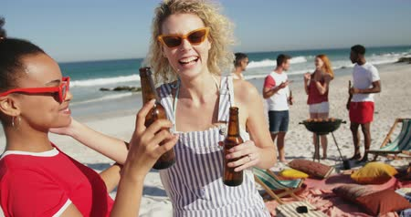 пляжная одежда : Close up front view of two female friends, a young African American and a young Caucasian woman, standing on a beach wearing sunglasses, making a toast with their beer botttes and embracing. Young friends having summer fun on the beach together 4k