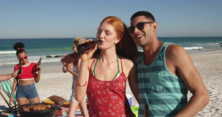 пляжная одежда : Close up of a young Asian man and a Caucasian woman embracing and drinking bottles of beer at a barbecue on a beach with their friends. Young friends having summer fun on the beach together 4k