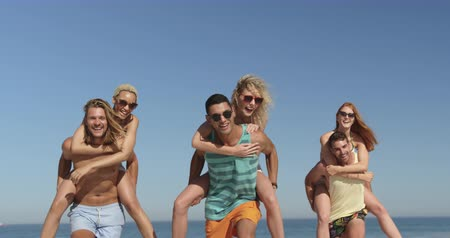 suntan : Close up of a multi-ethnic group of six happy young adult friends having fun piggyback racing on a beach. Young friends having summer fun on the beach together 4k Stock Footage