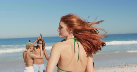 roupa de praia : Close up of a young Caucasian woman with long red hair holding a bottle of beer and dancing on a beach with her friends. Young friends having summer fun on the beach together 4k