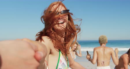 roupa de praia : Point of view close up of holding the hand of a young Caucasian woman, who joins her multi-ethnic young adult friends dancing on a beach. Young friends having summer fun on the beach together 4k Vídeos