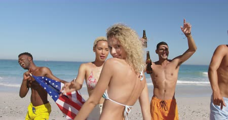 roupa de praia : Close up of a multi-ethnic group of happy young adult friends dancing on a beach, drinking beers, waving a US flags and laughing. Young friends having summer fun on the beach together 4k Vídeos