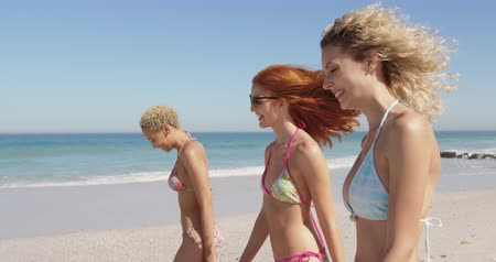 mayo : Close up side view of a multi-ethnic group of three happy young adult female friends walking on a beach in bikinis talking. Young friends having summer fun on the beach together 4k