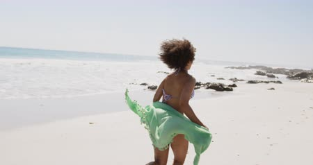 bronzeada : Close up back view of young African American woman holding beach wrap and running along a beach 4k