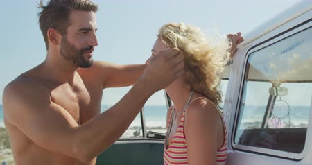 roupa de praia : Close up side view of smiling young Caucasian couple talking and relaxing, leaning on their camper van at a beach, man touching woman\\\\\\\s hair. Summer Road Trip in Camper Van to the beach with friends 4k
