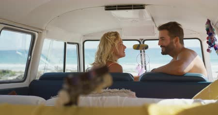 roupa de praia : Close up side view from inside vehicle of a young Caucasian couple talking sitting in the front seats of their camper van at a beach. Summer Road Trip in Camper Van to the beach with friends 4k
