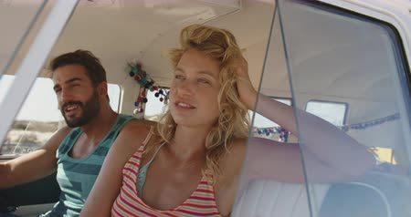 roupa de praia : Close up of a young Caucasian couple sitting in the front seat of a camper van at a beach relaxing and looking out of the window. Summer Road Trip in Camper Van to the beach with friends 4k