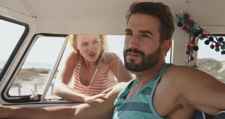 пляжная одежда : Close up of a young Caucasian woman talking through the side window to a young Caucasian man sitting in the front seat of a camper van. Summer Road Trip in Camper Van to the beach with friends 4k