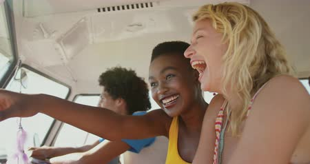 пляжная одежда : Close up side view of a three multi-ethnic male and female friends sitting in the front seat of a camper van, looking out of the window, pointing and laughing. Summer Road Trip in Camper Van to the beach with friends 4k Стоковые видеозаписи