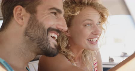 bronzeada : Close up side view of a young Caucasian couple sitting in the front seat of a camper van, laughing and looking out of the window. Summer Road Trip in Camper Van to the beach with friends 4k