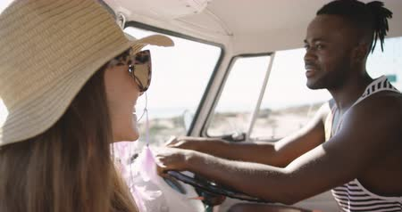 bronzeada : Over the shoulder view of a young Caucasian woman talking to a smiling young African American man sitting in the driving seat of a camper van, parked at a beach. Summer Road Trip in Camper Van to the beach with friends 4k