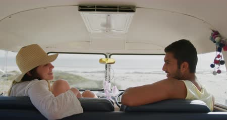пляжная одежда : Close up side view of a young Caucasian woman and a young Asian man talking and smiling at each other, sitting inside a camper van parked at a beach. The woman strecthers her legs out and puts her feet up on the dashboard. Summer Road Trip in Camper Van t